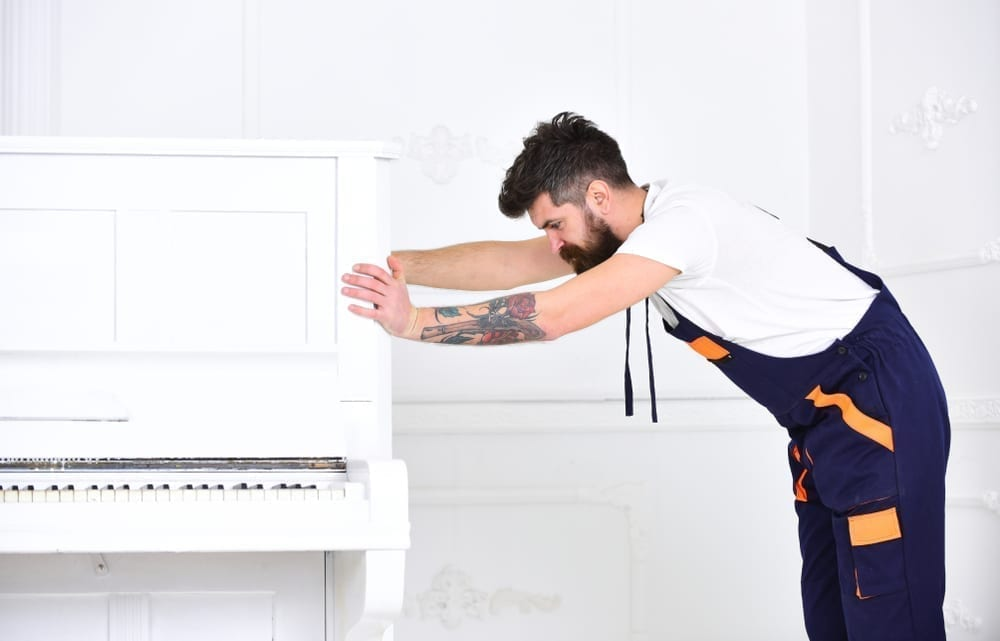 Worker in overalls pushes piano
