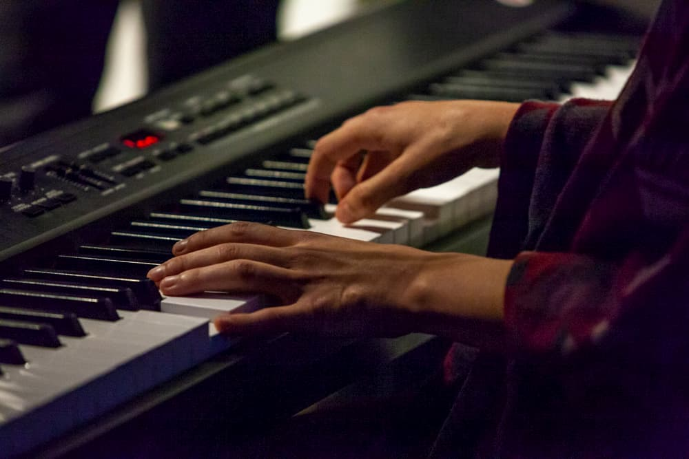 Young woman is playing digital piano in a pub - Closeup picture shot live during a concert